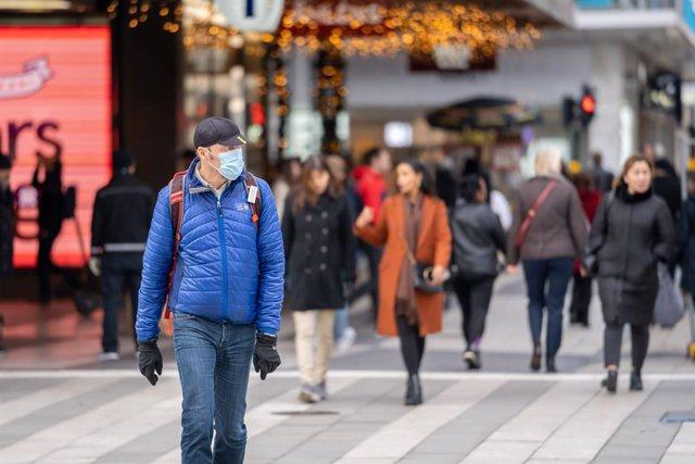 Un hombre con mascarilla en el centro de Estocolmo