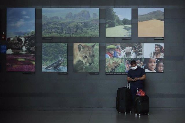 Un hombre con mascarilla espera con maletas frente al aeropuerto de Bogotá, Colombia.