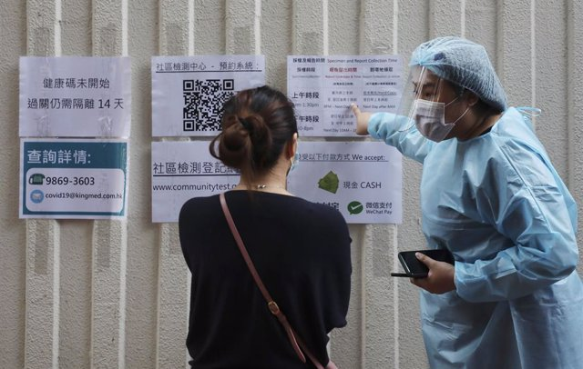 Personal médico de Hong Kong da indicaciones a quienes se acercan a sus instalaciones para someterse a una prueba de COVID-19.