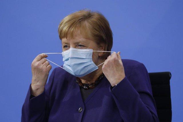 Angela Merjel se quita la mascarilla antes de una comparecencia en Berlín