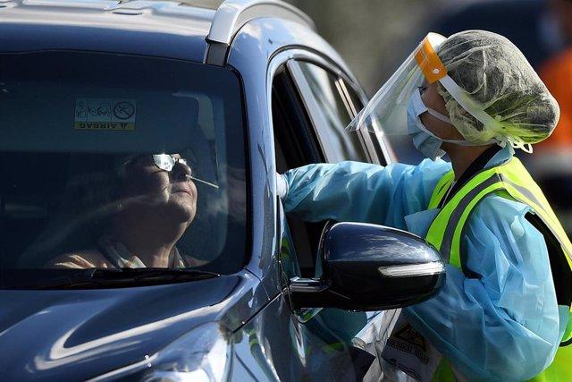 Una trabajadora con equipo de protección toma una muestra para un test de coronavirus en Sídney