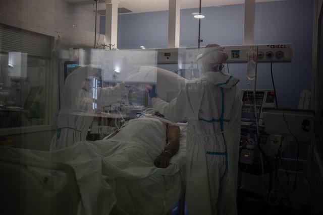 Trabajadores sanitarios protegidos atienden a un paciente en la UCI