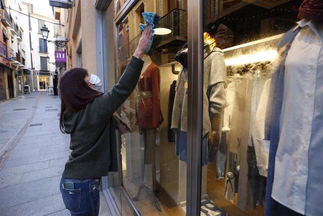 Una dependienta limpiando un escaparate de una tienda