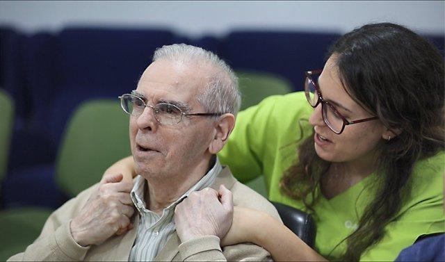 Una cuidadora atiende a un anciano dependiente en una residencia