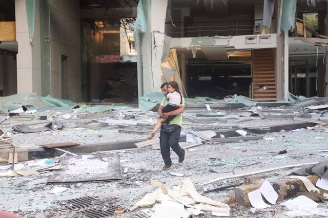 Imagen de un padre con su hija entre los escombros provocados tras la explosión que sacudió el puerto de Beirut el pasado agosto.