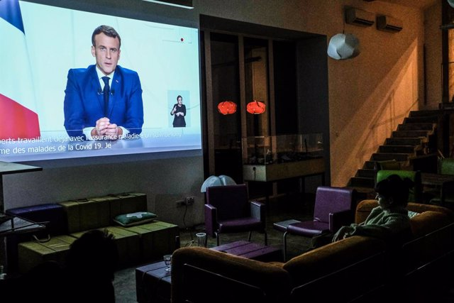 24 November 2020, France, Paris: A woman watches a televised address to the nation by French President Emmanuel Macron, on a video projector at her house. Photo: Sadak Souici/Le Pictorium Agency via ZUMA/dpa