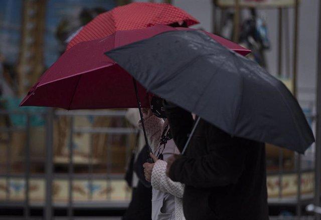 Peatones con paraguas.