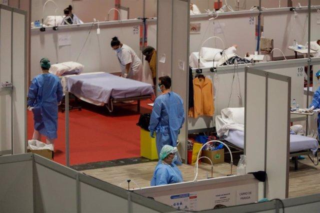 Sanitarios trabajan atendiendo pacientes en el Pabellón 9 del hospital de campaña de IFEMA, en el que los enfermos de coronavirus son ahora atendidos únicamente en el Pabellón 9 tras el cierre del 7 al bajar la presión asistencial y que estará operativo p