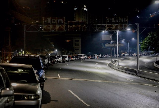 22 April 2020, Venezuela, Caracas: People stand beside their cars in long queue in front of a gas station. The largest Russian oil company Rosneft, one of the last and largest foreign investors in Venezuela, has withdrawn from the South American country a