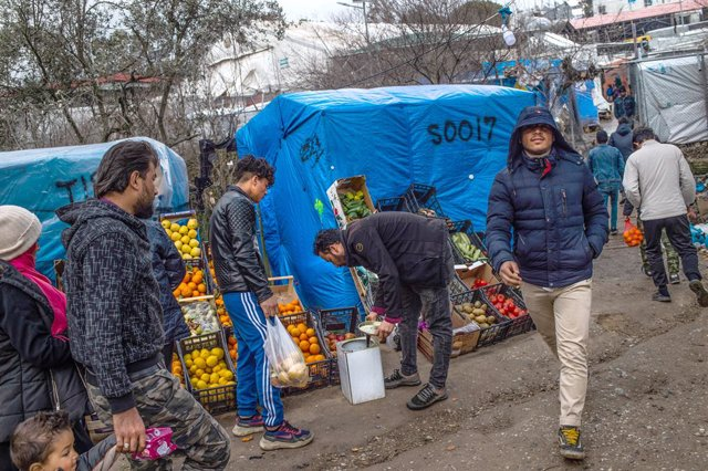 27 February 2020, Greece, Lesbos: A migrant buys fruit and vegetables at a stand in a temporary tent camp near the camp for migrants in Moria. Following serious clashes between police and angry inhabitants of the Greek island of Lesbos, which left dozens