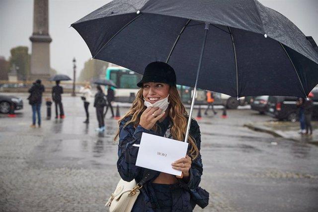 Una mujer con mascarilla y paraguas en París, Francia