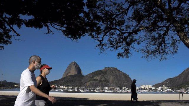 Un grupo de personas camina por las playas de Botafogo, Río de Janeiro, sur de Brasil.