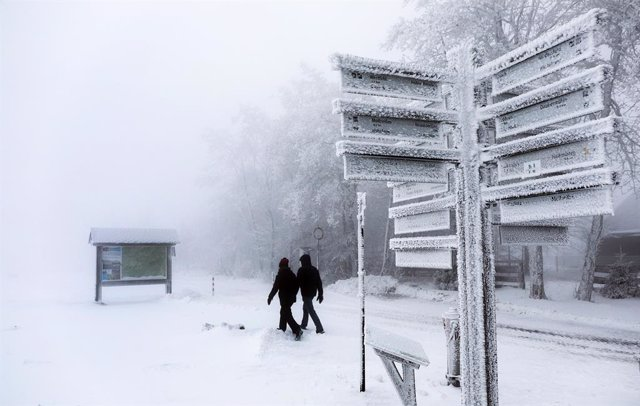 04 December 2020, North Rhine-Westphalia, Winterberg: Walkers walk by an icy signpost at the closed Kahler Asten ski area due to coronavirus (COVID-19) restrictions. Photo: Oliver Berg/dpa