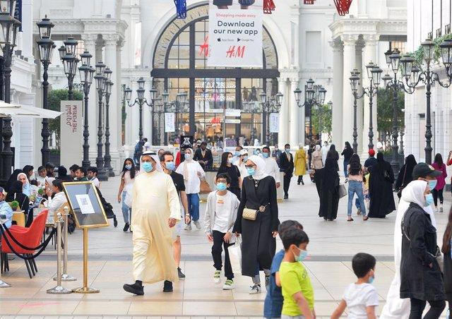Personas con mascarilla en un centro comercial en Kuwait