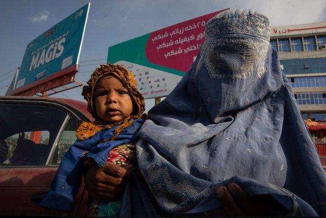 Mujer afgana con niño en Kabul