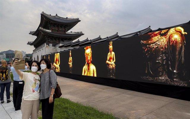 Dos mujeres con mascarilla se hacen un selfi en un museo callejero en Seúl