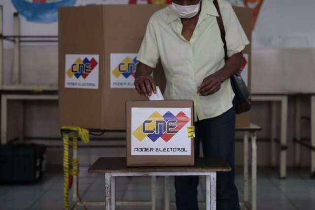 06 December 2020, Venezuela, Caracas: A woman casts her vote into a ballot box inside a polling station during the 2020 Venezuelan parliamentary election. Most opposition parties as well as interim president Guaido expect electoral fraud and have therefor
