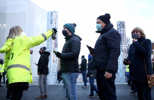 Fans del Tottenham Hotspur esperando a que les tomen la temperatura para entrar en el estadio a ver un partido