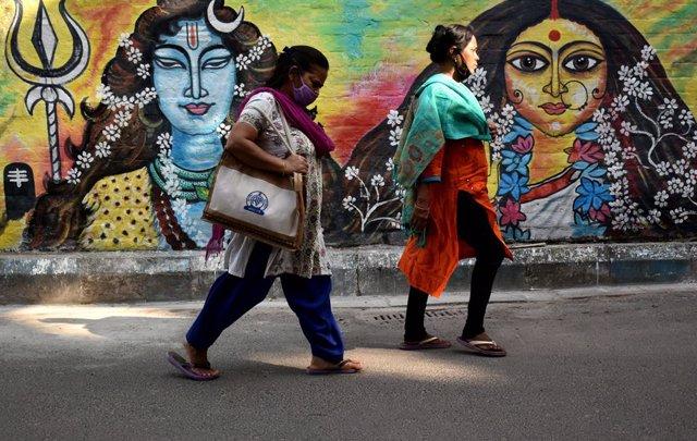 Dos mujeres pasean frente a un mural en India llevando mascarilla debido a la crisis sanitaria provocada por el coronavirus.