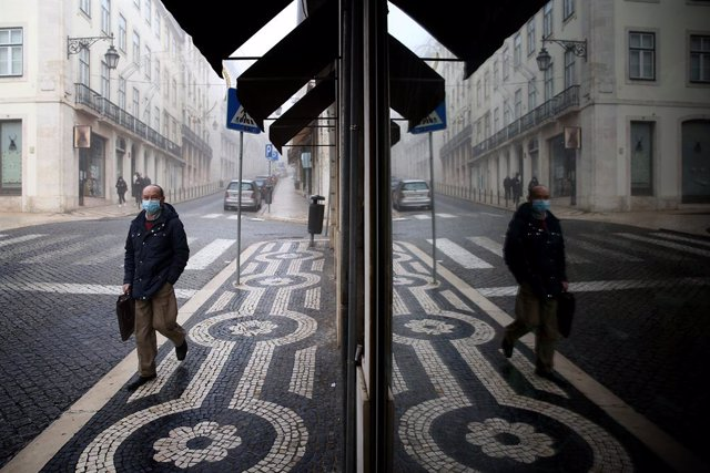 09 November 2020, Portugal, Lisbon: A man wearing a face mask reflected in a shop glass as he walks in downtown Lisbon. Portugal returned to the state of emergency until 23 November amid the rising numbers of Coronavirus infections. Photo: Pedro Fiuza/ZUM