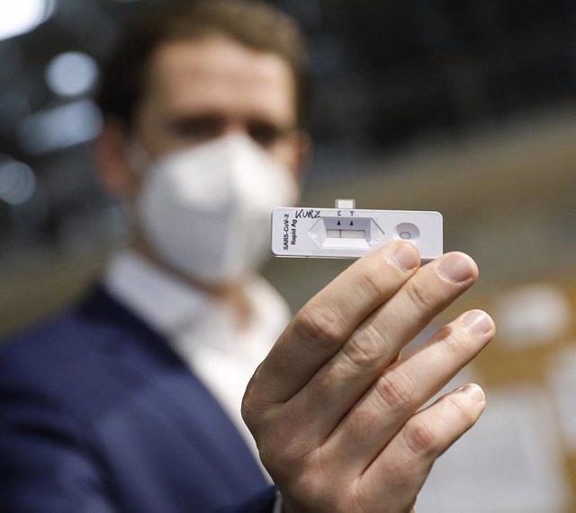 07 December 2020, Austria, Vienna: Austrian Chancellor Sebastian Kurz holds a coronavirus test during a visit to a Covid-19 test centre set up at the fair grounds of Vienna. Photo: Dragan Tatic/BKA/APA/dpa