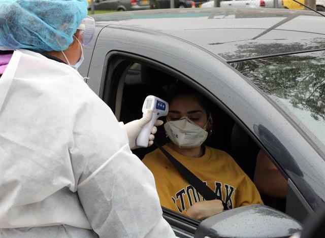 Una trabajadora médica tomando la temperatura a una mujer colombiana en el contexto de la pandemia del coronavirus.