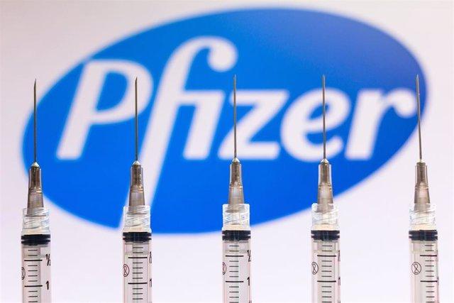 Imagen de archivo de unas vacunas frente al logo de la farmacéutica Pfizer.