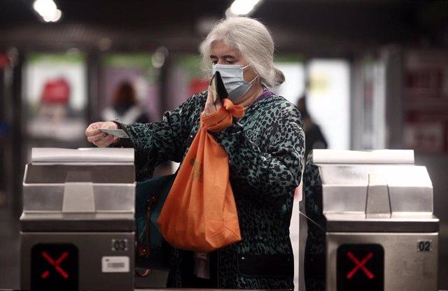 Una anciana con un billete en los torniquetes del metro de Oporto, Madrid (España), a 17 de noviembre de 2020.