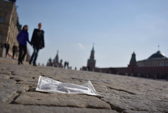 28 March 2020, Russia, Moscow: A couple walks in the sunshine across the Red Square past a discarded face mask. In the Russian capital, stricter regulations to combat the coronavirus (COVID-19) pandemic. Photo: Christian Thiele/dpa