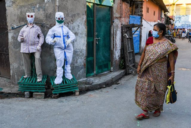 13 November 2020, India, Kolkata: A lady wearing face mask passes by figurines wearing PPE and mask, amid the Coronavirus (Covid-19) outbreak. Photo: Debarchan Chatterjee/ZUMA Wire/dpa