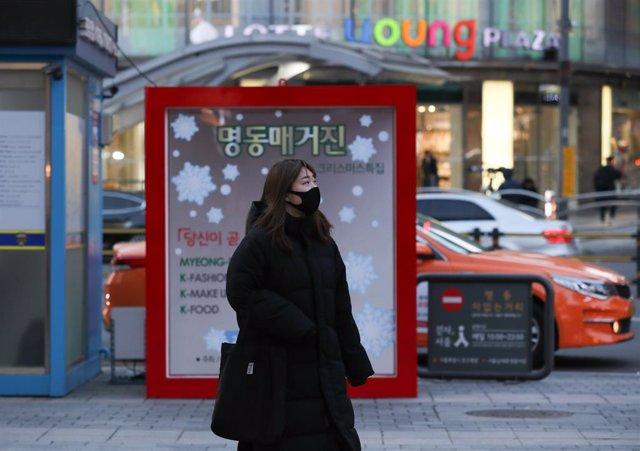 Una mujer pasea por el área comercial del barrio de Myeongdong, en Seúl, la capital de corea del Sur.