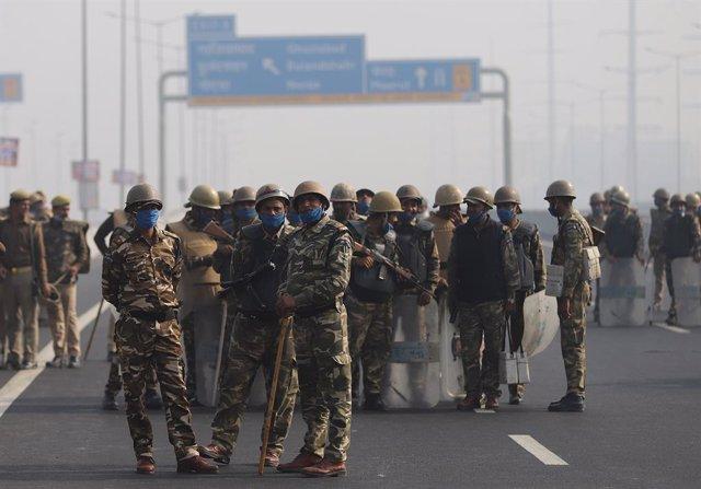 Agentes de las fuerzas de seguridad indias desplegados con mascarilla en Nueva Delhi frente a una protesta de agricultores