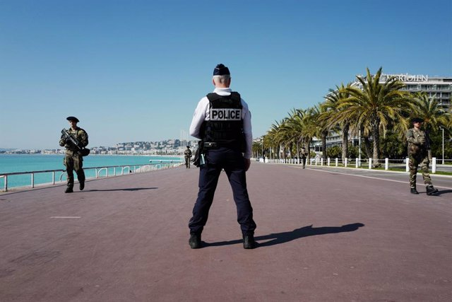 """18 March 2020, France, Nizza: A policeman stands by while soldiers patrol the famous """"Promenade des Anglais"""" on the French Riviera. A nationwide 15-day curfew has been in force in France since noon on Tuesday. Photo: Valery Hache/AFP/dpa"""