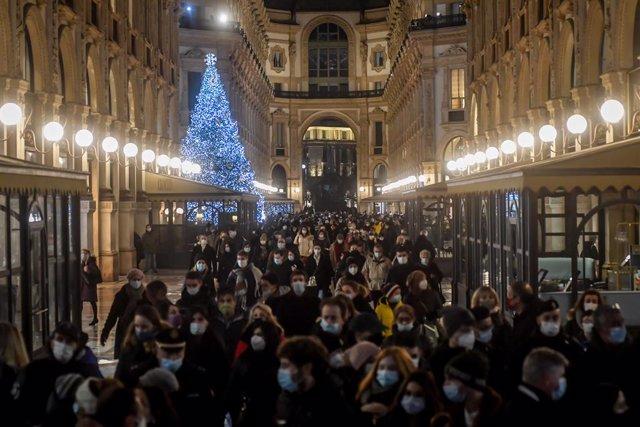Ciudadanos con mascarilla haciendo compras navideñas en Milán
