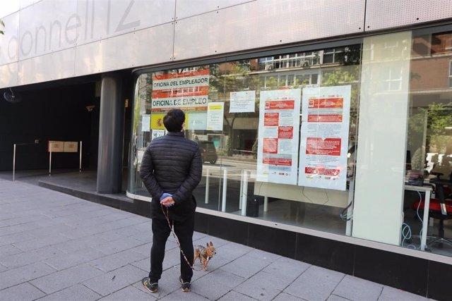 Un hombre pasa con su perro frente a una oficina de Empleo en Madrid