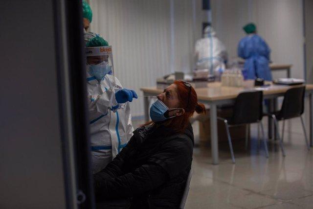 Una mujer recibe una prueba PCR en un dispositivo de cribados masivos en el barrio del Raval, en Barcelona