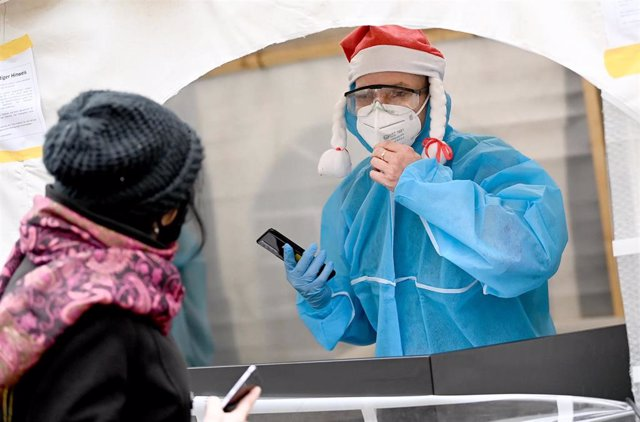 "09 December 2020, Berlin: A medical personnel wearing protective suit registers a woman for a smear, in the entrance area of the nightclub ""KitKat-Club"" which offers medically-supervised rapid antigen tests for a fee."