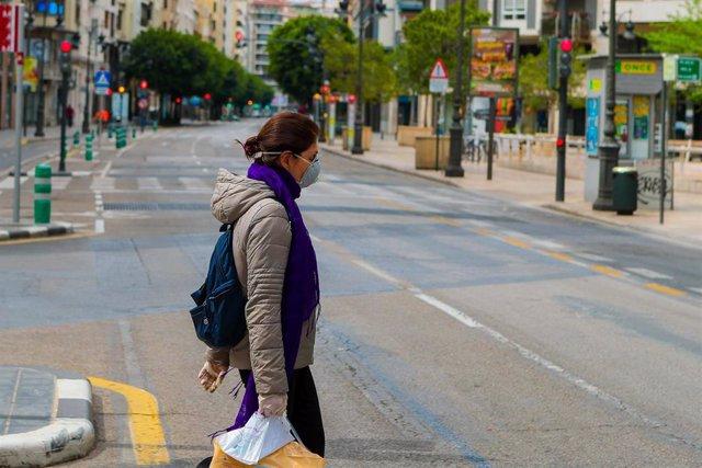 Una mujer protegida con mascarilla sanitaria camina por una de las calles desiertas de Valencia durante el Viernes Santo por el confinamiento impuesto por el Estado de Alarma provocado por el coronavirus, COVID19. En Madrid (España) a 10 de abril de 2020.