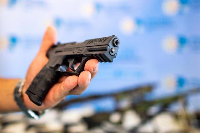 Un policía alemán sostiene una pistola durante un registro domiciliario enmarcado en una campaña contra el comercio ilegal de armas.