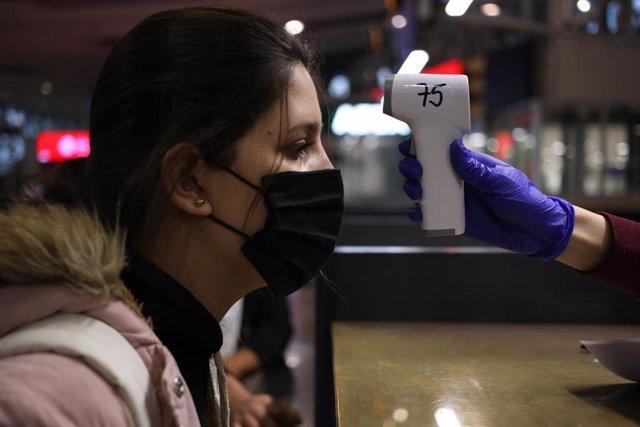 Una mujer colombiana se somete a un control de temperatura antes de abordar un avión de regreso a su país desde Santiago de Chile.