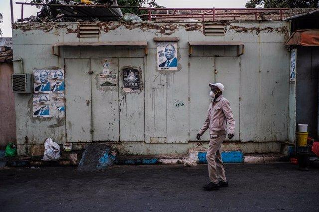 Un hombre camina junto a una tienda cerrada a causa de la pandemia de coronavirus en la capital de Senegal, Dakar