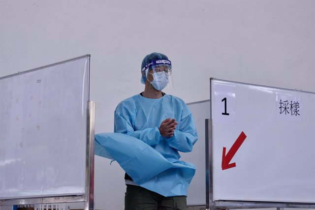 04 December 2020, China, Hong kong: A medical worker in protective gear rubs disinfectant into his hands as he stands in a temporary cubicle for a coronavirus test station. Photo: Liau Chung-Ren/ZUMA Wire/dpa