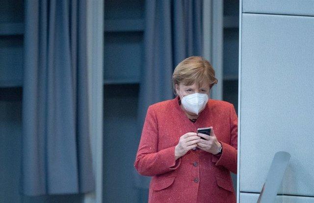 Angela Merkel revisa su teléfono móvil durante una sesión en el Bundestag