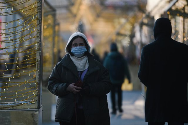 Una mujer con mascarilla pasea por Moscú