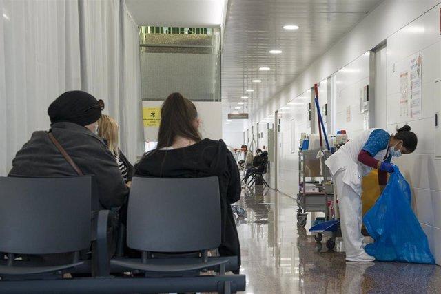 Varias pacientes esperan en una sala de espera mientras una mujer limpia en el CAP Masdevall el día en el que comienza la campaña de vacunación antigripal en la región, en Figueres, Girona (Catalunya), a 16 de octubre de 2020.La campaña coincide con la en