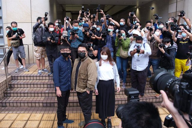 23 November 2020, China, Hong Kong: (L-R) Pro-democracy activists Joshua Wong, Ivan Lam and Agnes Chow arrive at the West Kowloon Magistrates' Courts for charges in connection with a protest outside police headquarters in June 2019. Photo: Isaac Wong/SOPA