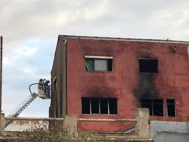 Feines d'extinció de l'incendi d'una nau a Badalona