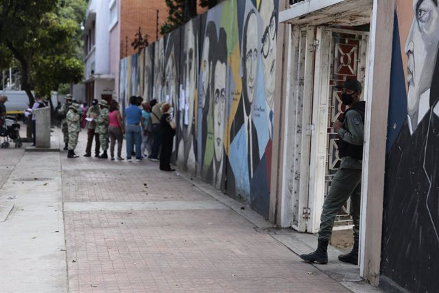 06 December 2020, Venezuela, Caracas: A soldier waits for the voters outside a polling station during the 2020 Venezuelan parliamentary election. Most opposition parties as well as interim president Guaido expect electoral fraud and have therefore called