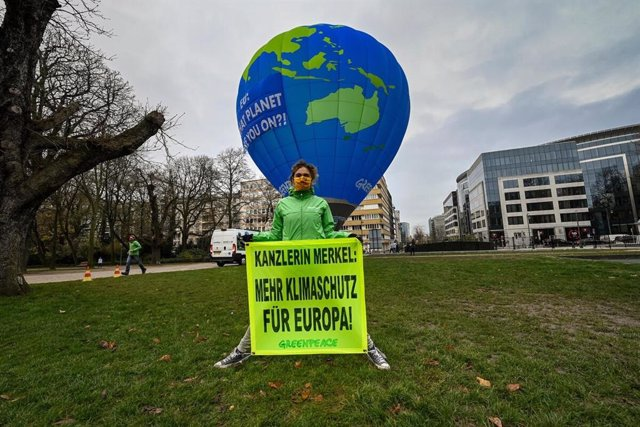 Activistas de Greenpeace despliegan en Bruselas (Bélgica) un globo aerostático para denunciar la falta de ambición climática de los Veintiesiete a los que reclaman una reducción de CO2 más elevada para 2030.
