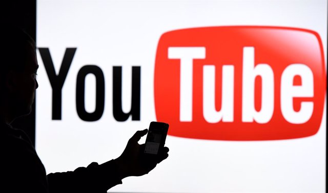 FILED - 15 March 2019, Schleswig-Holstein, Aukrug-Homfeld: A man with holds a smartphone in front of the logo of the internet platform YouTube. Photo: Carsten Rehder/dpa